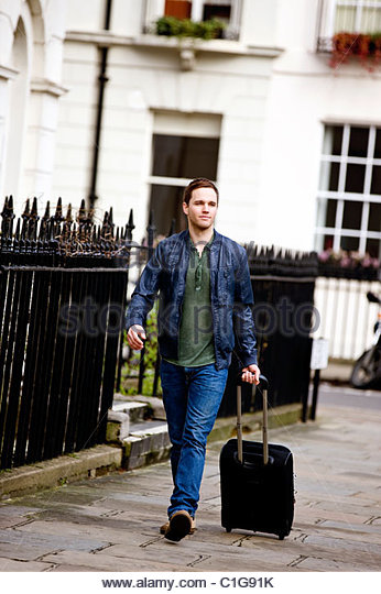 A young man pulling his suitcase in the street - Stock-Bilder