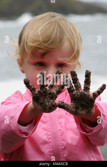 A girl stares in wonder at the sand on her hands - Stock-Bilder