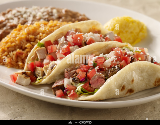 One steak and one chicken taco topped with salsa fresca and cheese served with refried beans and Spanish rice - Stock Image
