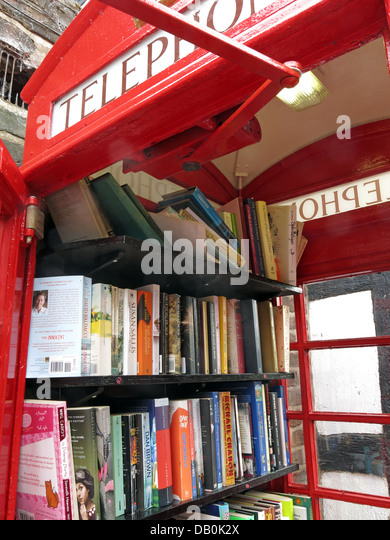Interior of an old red British Telephone box turned into a British village eccentric lending library - Stock Image