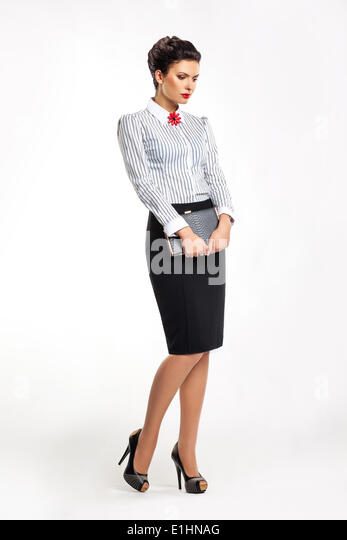 Thoughtful businesslady in fashion skirt and blouse with book dreaming - Stock Image
