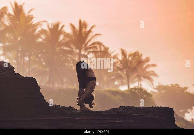 Indonesia, Bali, woman practising yoga at the coast at twilight - Stock Image