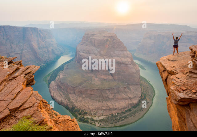 Woman Stands Over the Edge of Horseshoe Bend during a smoky sunset - Stock Image