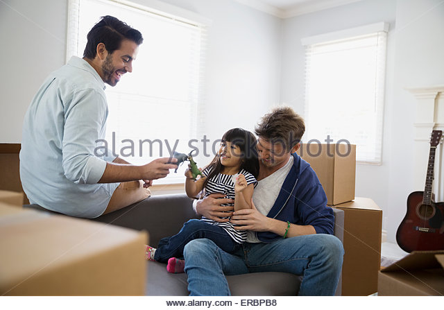 Homosexual couple playing with daughter sofa moving boxes - Stock Image