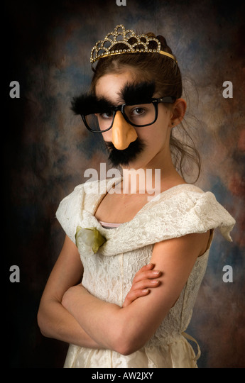 young girl playing dress up with mask or disguise - Stock Image