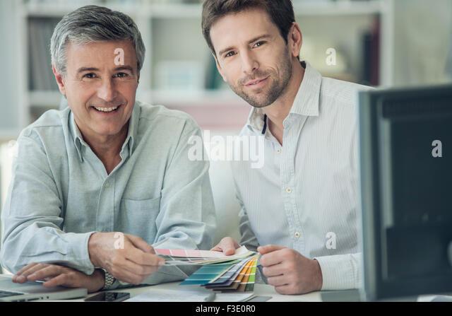 Businessmen discussing color swatches, portrait - Stock-Bilder