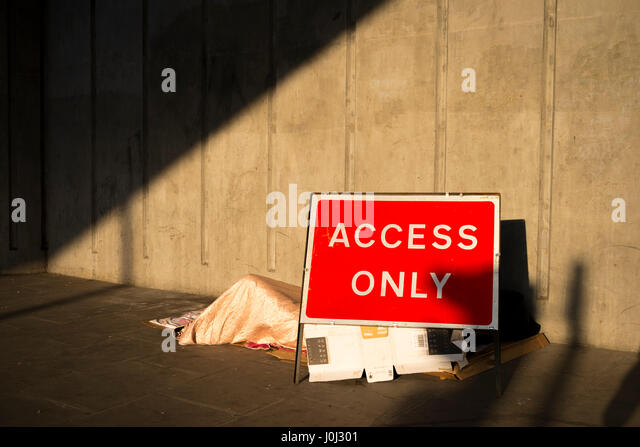 A homeless person sleeps between an Access Only road sign and a solid concrete wall - Liverpool Street, London April - Stock Image