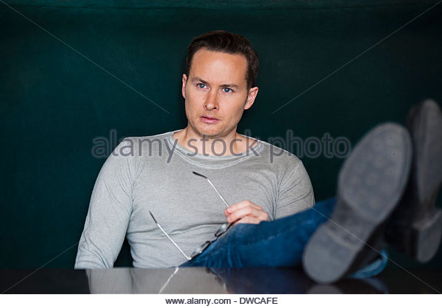 Thoughtful mid adult man with feet up on cafe table - Stock Image