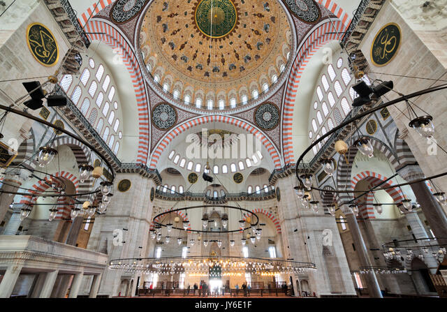 Istanbul, Turkey - April 19, 2017: Interior of Suleymaniye Mosque, with a huge pillars, arches, windows and tourists - Stock Image