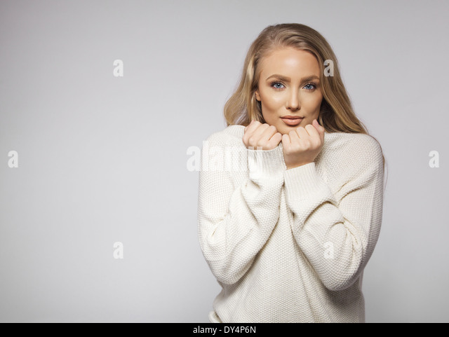 Portrait of beautiful young blond wearing sweater feeling cold. Cute young female fashion model posing on gray background. - Stock Image