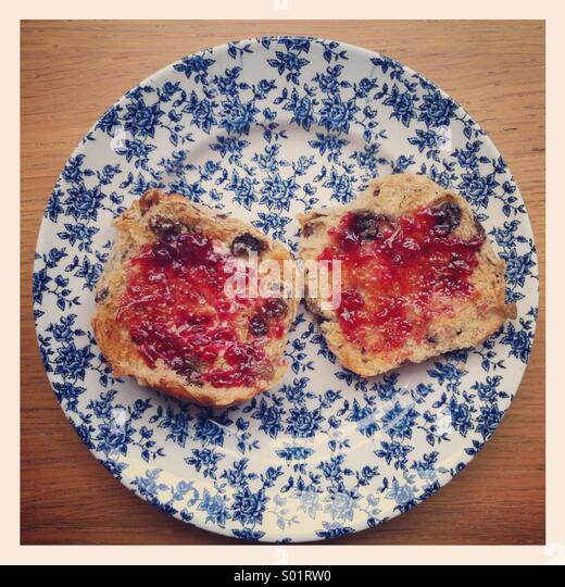 Jam on two toasted halves of a hot cross bun, on a vintage blue and white floral plate. - Stock-Bilder