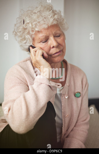 Grandmother using a cell phone in communicating - Stock-Bilder