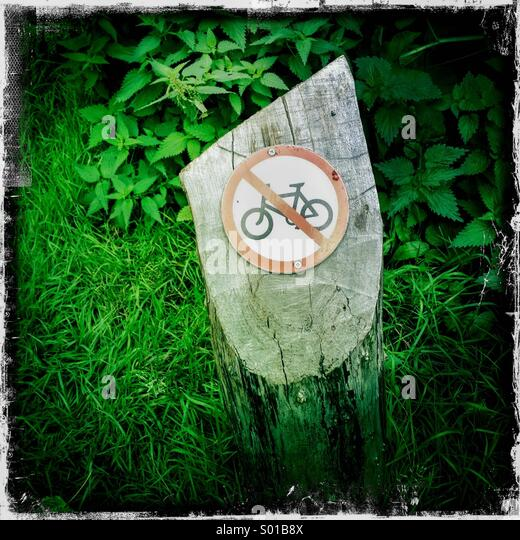 No cycling bike icon on tree stump. Hamptead Heath, London, UK. Hipstamatic, iPhone. - Stock Image