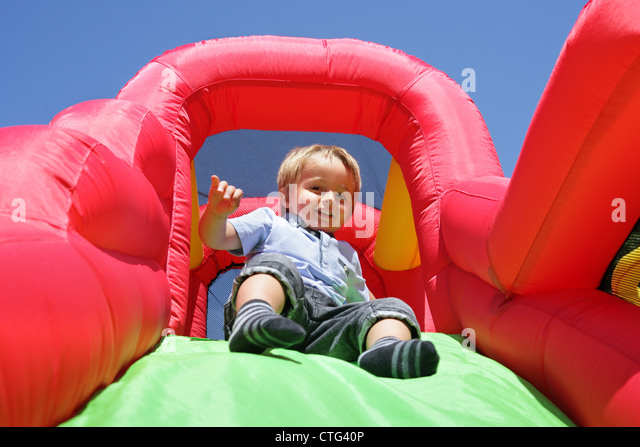 Child on inflatable bouncy castle slide - Stock Image