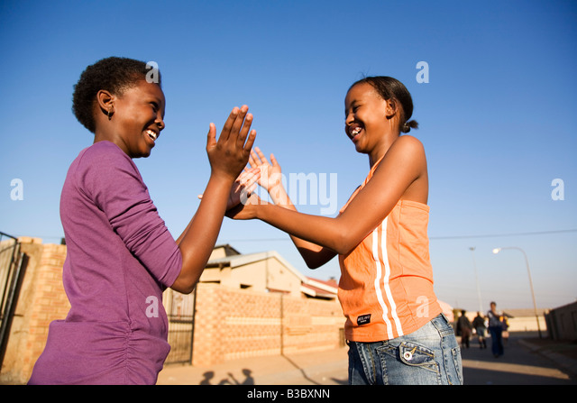 Two girls clapping hands, smiling, side view - Stock-Bilder