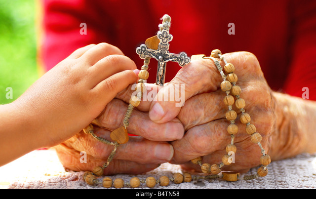 child hands holding old catholic woman hand who holds rosary - Stock-Bilder