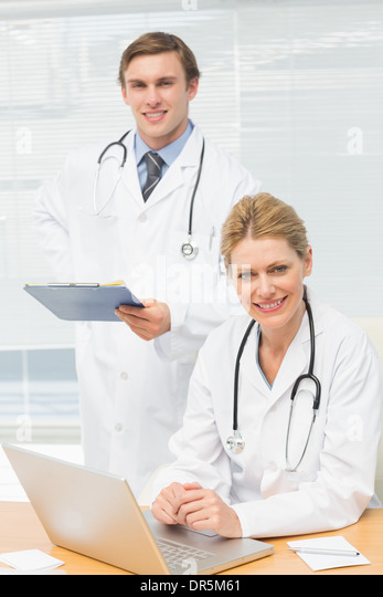 Doctors smiling at the camera together - Stock Image