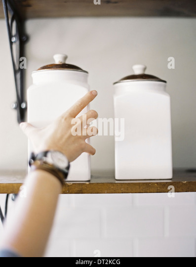 A domestic kitchen A person reaching up to two storage jars on a shelf - Stock Image