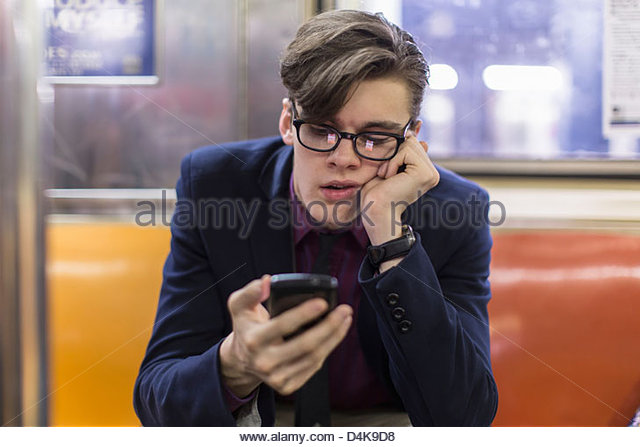 Businessman using cell phone on subway - Stock Image