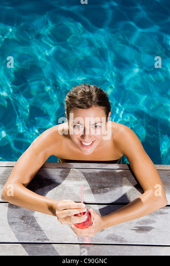 Young woman with soft drink at poolside - Stock Image