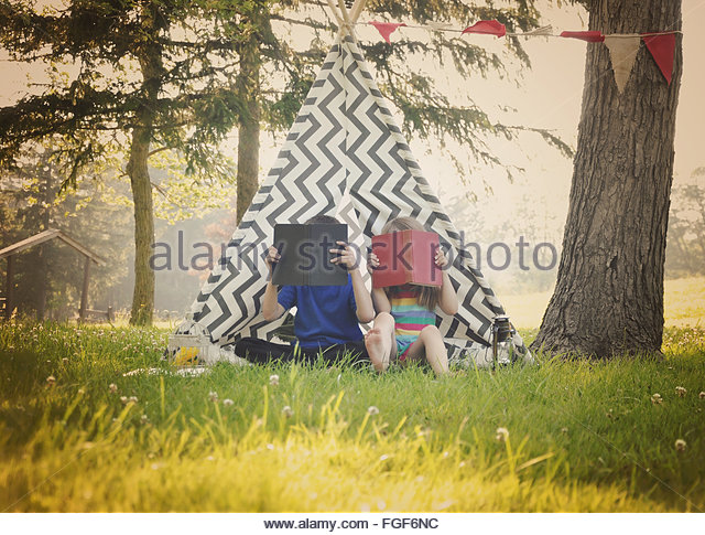 Two young children are reading books together outside in a teepee tent for a education or learning concept. - Stock Image