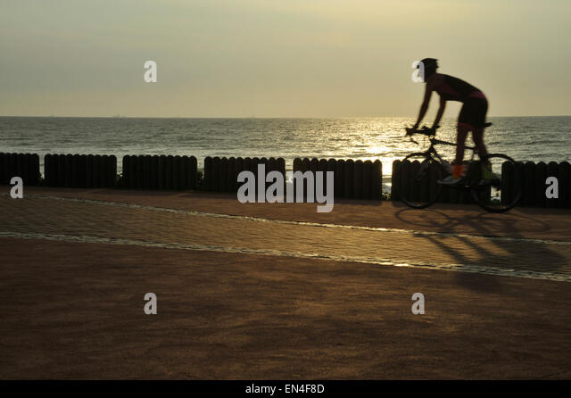 Lone adult cyclist riding bicycle on Durban beachfront promenade early in morning South Africa Sports Lifestyle - Stock-Bilder