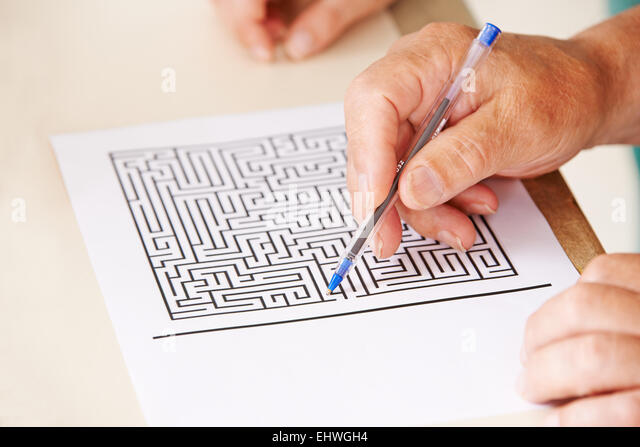 Hand of senior man with pen doing memory training with a paper maze - Stock-Bilder