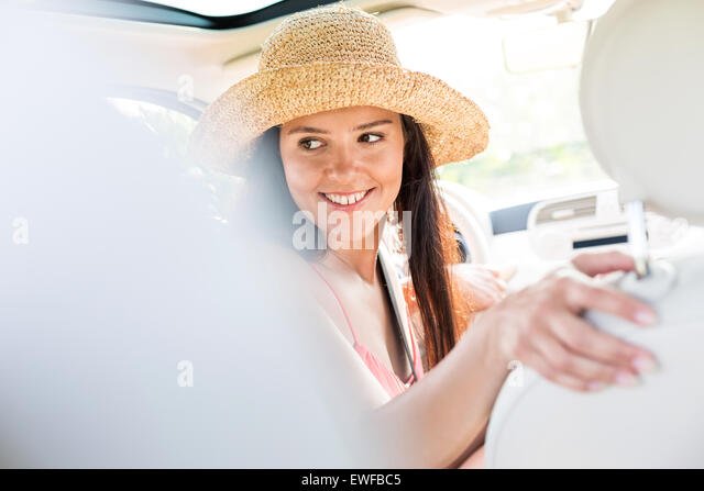 Happy woman looking back while driving car - Stock Image