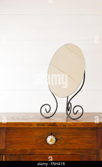 Retro mirror on bedside table,  background white wooden wall - Stock Image