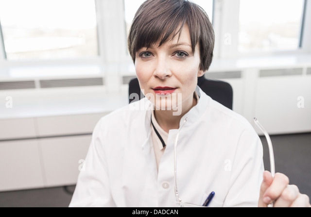 Mid adult woman wearing white coat sitting at desk - Stock Image