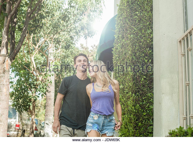 Young romantic couple, walking along street - Stock-Bilder