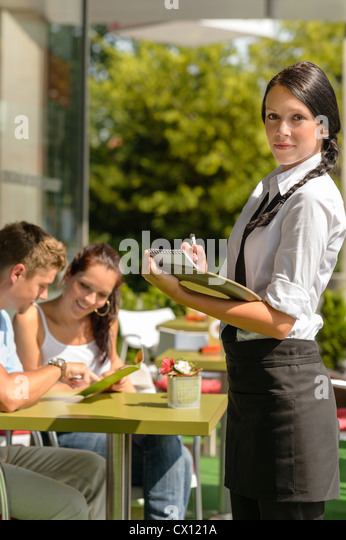 Waitress waiting for clients to decide cafe order restaurant terrace - Stock Image