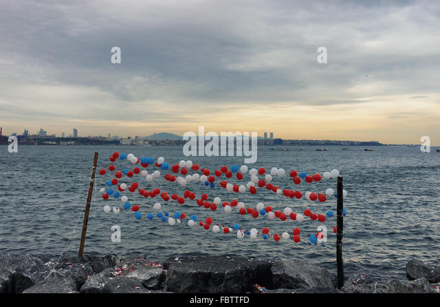 Colored balloons in the dash on the stony gray shores of the Bosphorus in Istanbul at the end of the day - Stock Image