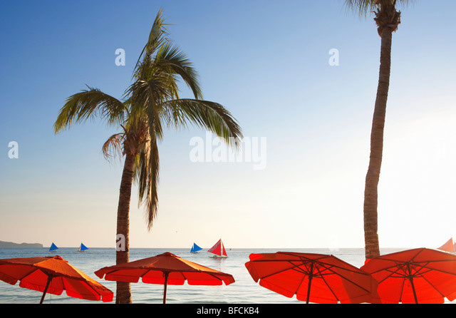 Red parasols and sail boats Boracay; The Visayas; Philippines. - Stock Image