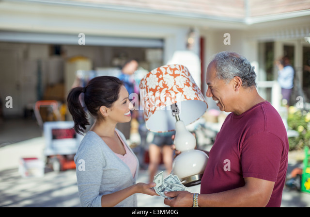 Man buying lamp at yard sale - Stock Image
