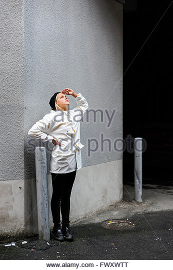 Sweden, Vastra Gotaland, Young woman in white coat standing by wall and looking up - Stock Image