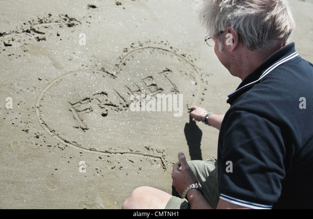 High angle view of man drawing heart on sand - Stock Image