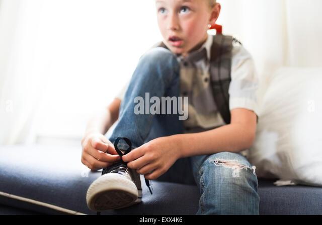 Boy (6-7) tying shoes - Stock Image