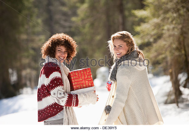Two women with gifts outdoors in snow - Stock Image