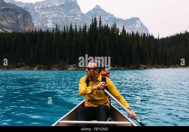 Front view of mid adult man paddling canoe, looking away, Moraine lake, Banff National Park, Alberta Canada - Stock Image