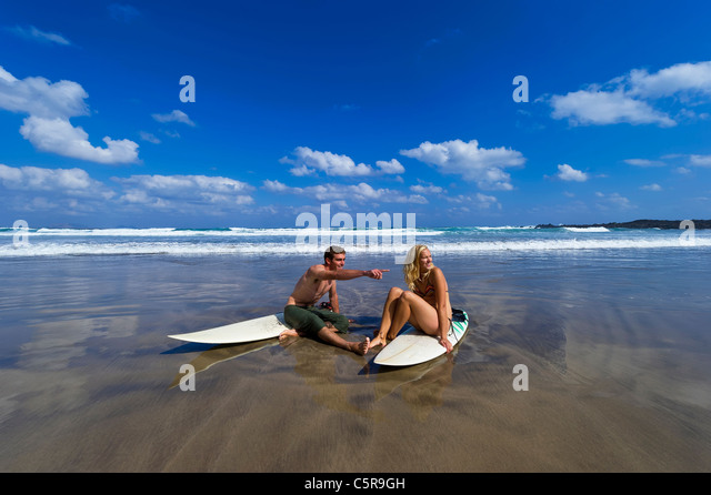 A surfing couple relax on the beach and take in the scenery. - Stock Image
