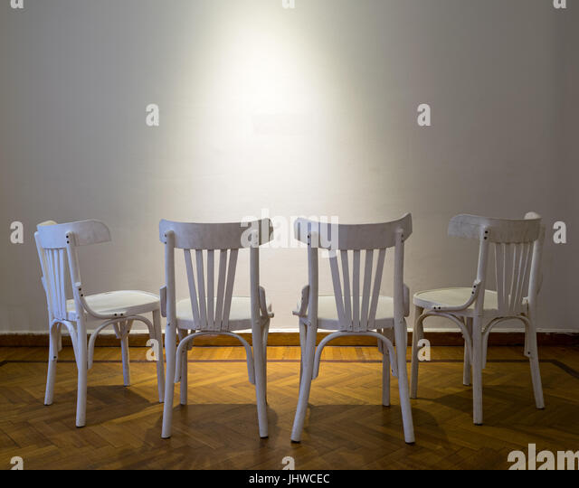 Four white wooden chairs facing spot lighted white wall on wooden parquet floor - Stock Image