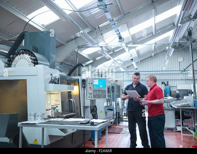 Engineers discussing work in front of CNC machines in engineering factory - Stock Image