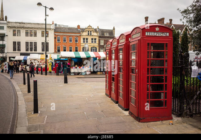 The University city of Cambridge in England with traditional red telephone boxes in the street near the market - Stock-Bilder