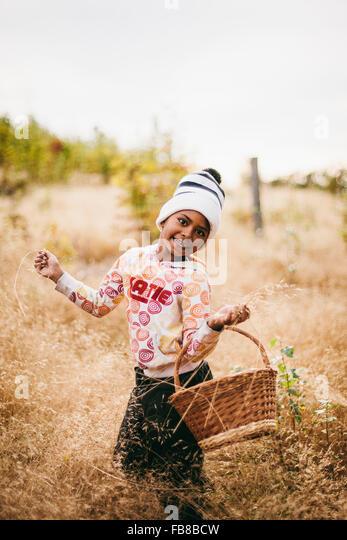 Sweden, Medelpad, Sundsvall, Juniskar, Portrait of smiling girl (6-7) holding basket - Stock Image