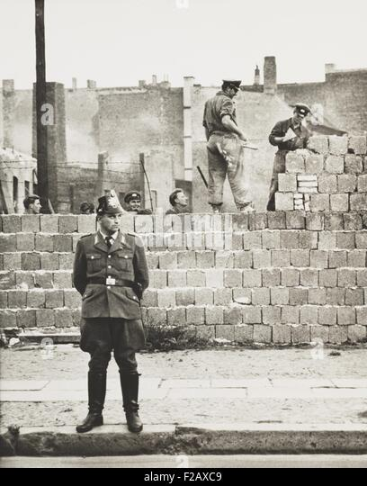 West Berlin policeman stands before the concrete block wall dividing East and West Berlin. Along Bernauer Strasse, - Stock-Bilder