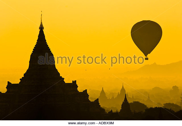 Hot air balloon and temple stupa in silhouette at sunrise. Bagan, Myanmar - Stock Image