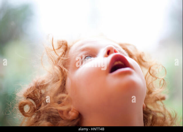A three year old girl loowing in awe at the sky above - Stock Image