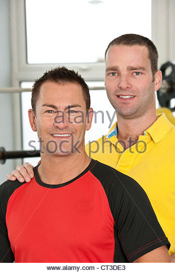 Trainer and client laughing in gym - Stock Image