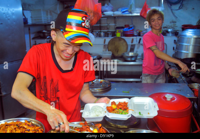 Singapore Jalan Besar Lavender Food Centre Center court vendors Asian man display kitchen cook job meat preparing - Stock Image